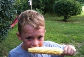 My son, chowing down on our first ear of corn.