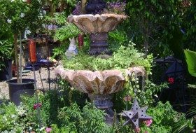 Three-tiered fountain filled with flowering container plants.