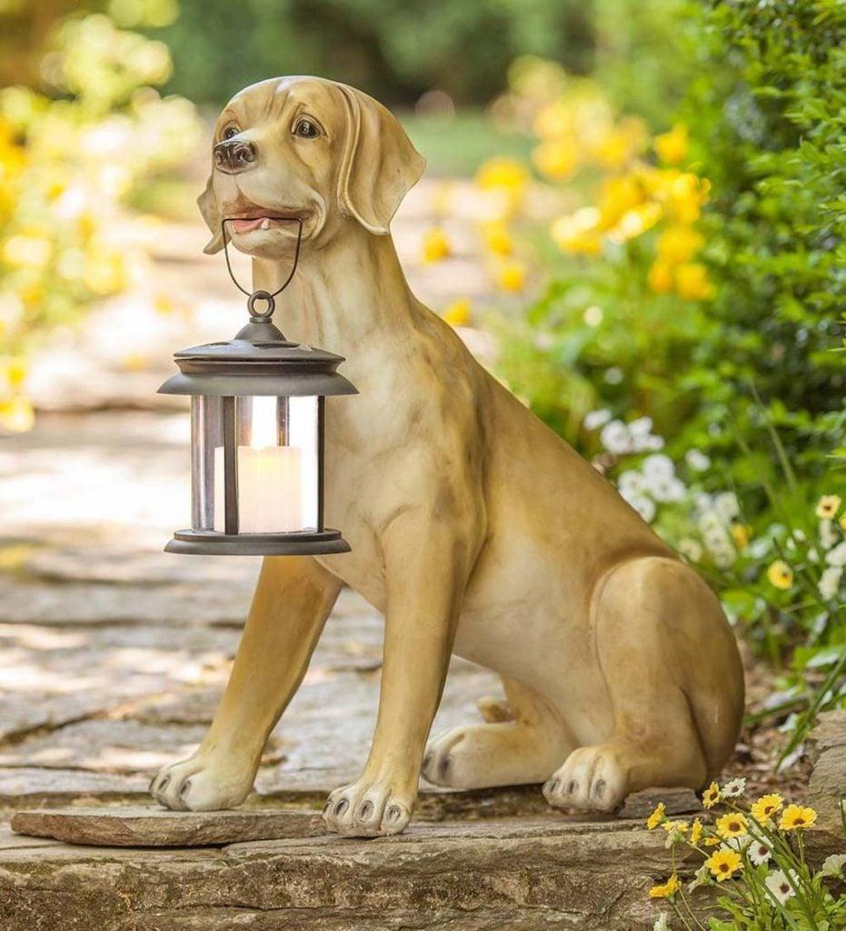 Yellow Labrador sculpture holding a solar lantern