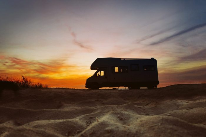 Camper van parked next to beach. Sunset in the background. Summer traveling concept.