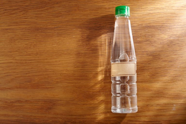 top view of white vinegar on the wooden background