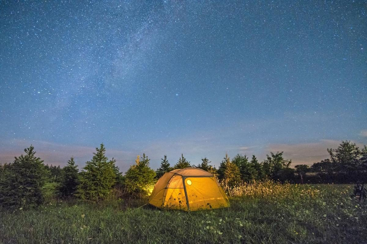 Illuminated camping tent under starry sky