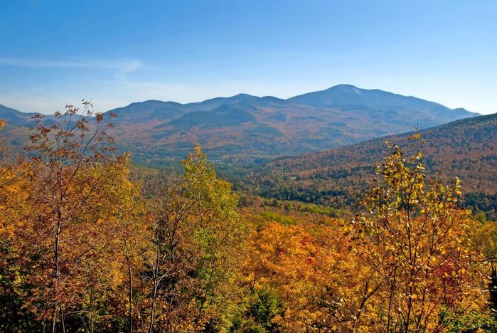 Colorful trees and hills looking out on Big Slide Trail, Keene Valley, New York, USA.