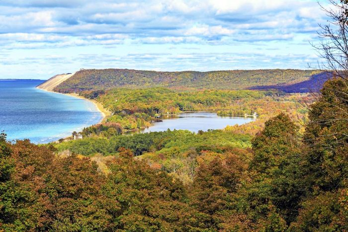A view of South Bar Lake and Lake Michigan, as seen from Empire Bluff Trail. Sleeping Bear Plateau, part of Sleeping Bear Dunes is a dominant part of the scene. South Manitou Island can be seen in the distance.