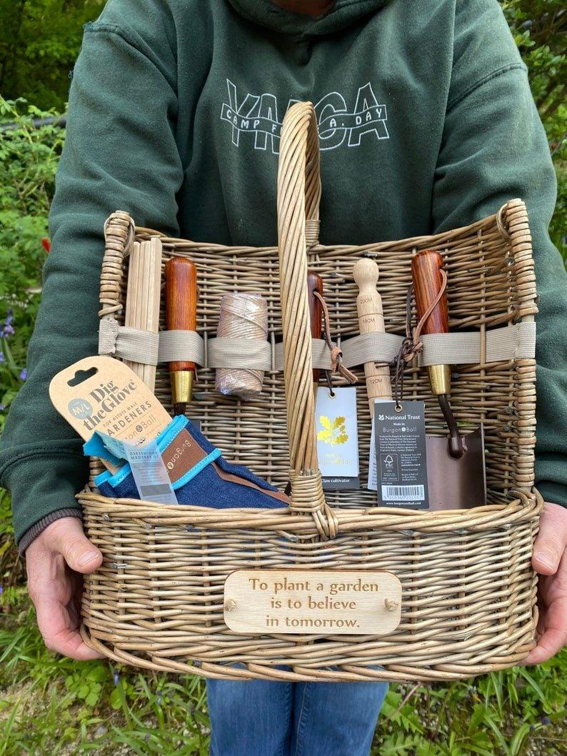 A gardener holds a wooden trug.