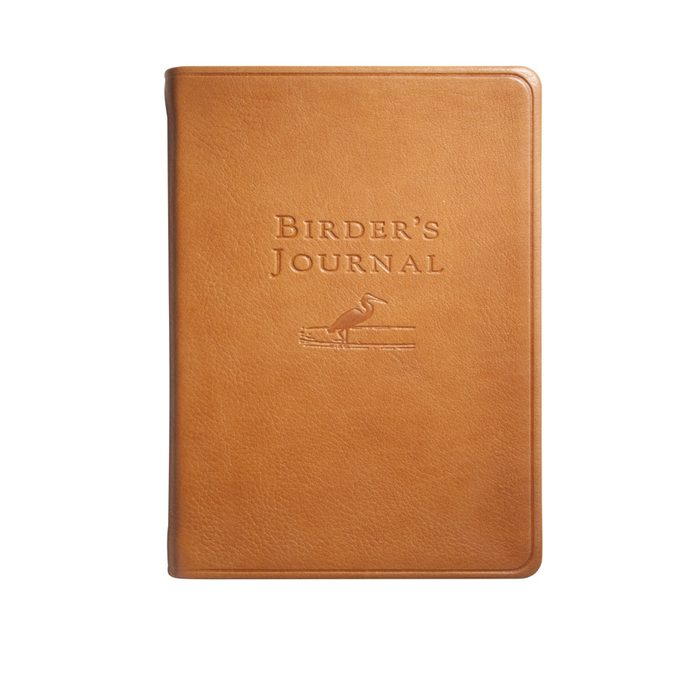 A tan leather-bound journal with a stamped bird on the cover.