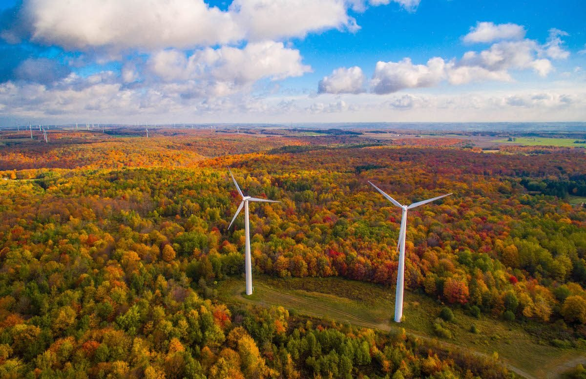 Wind turbines dot a landscape of fall foliage in New York.
