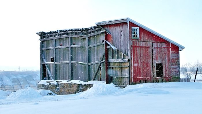 And old barn structure in the snow.