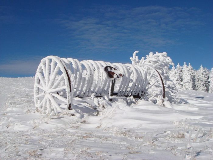 A hay rake in a field covered with hoarfrost.