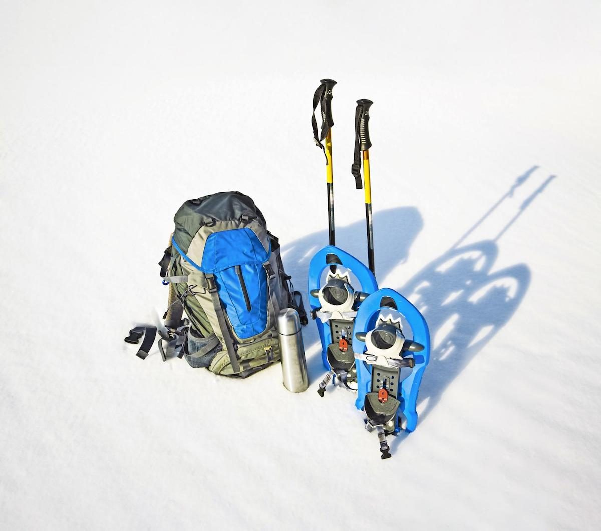 A backpack, showshoes and trekking poles in the snow.