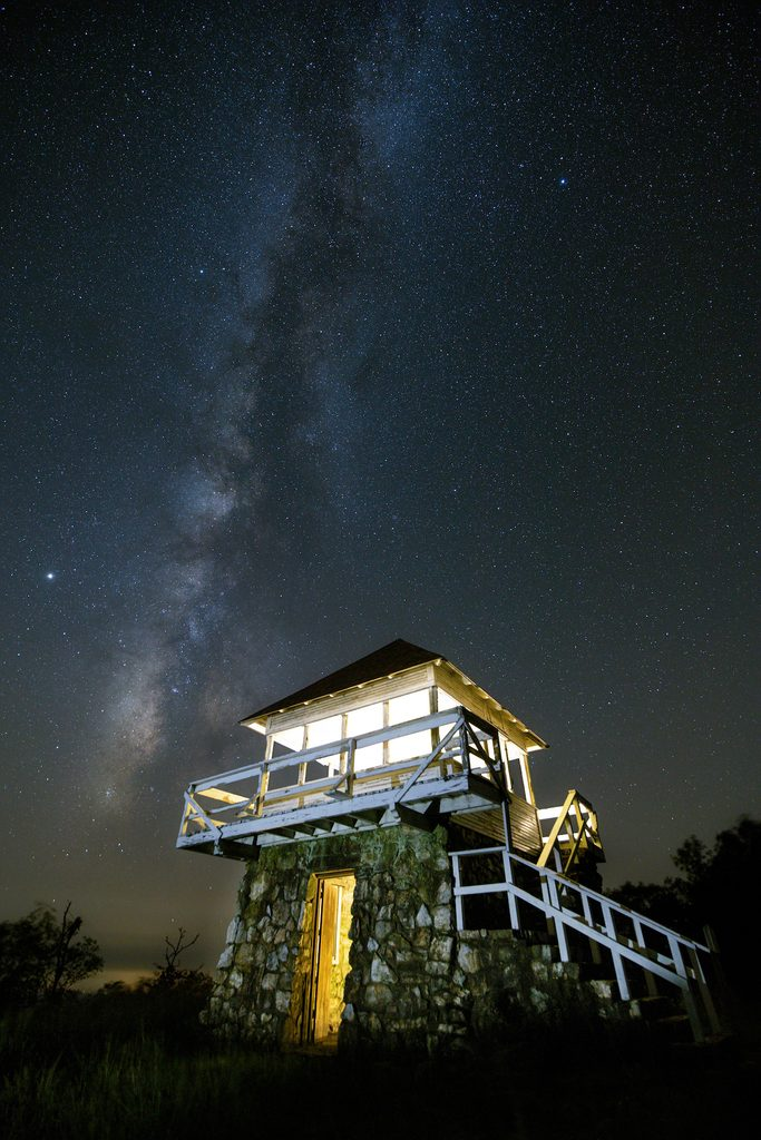 A night view of a fire tower and the milky way in Ouachita State Park.