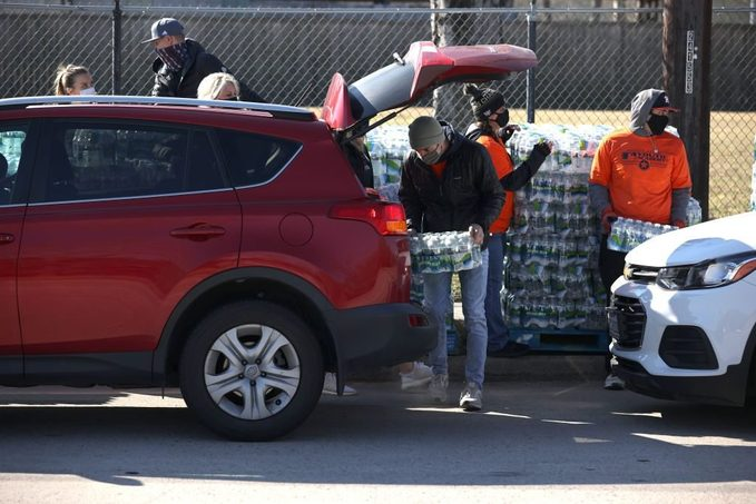 Volunteers load cases of water into a car during a water distribution at the Astros Youth Academy on February 20, 2021 in Houston, Texas.