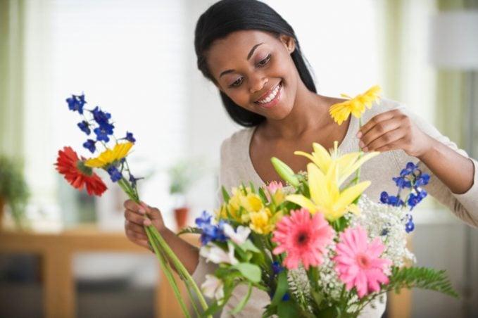 African American woman arranging fresh cut flowers