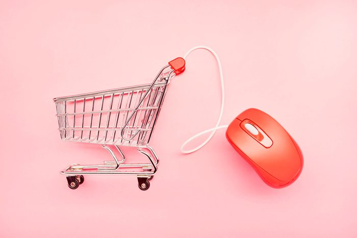 Still life of a small shopping cart and red computer mouse on pink background, online shopping