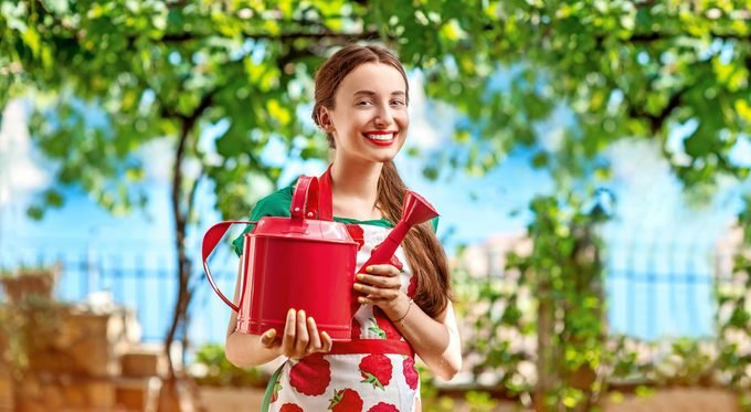 Portrait of a young woman gardener with apron and watering can in the garden