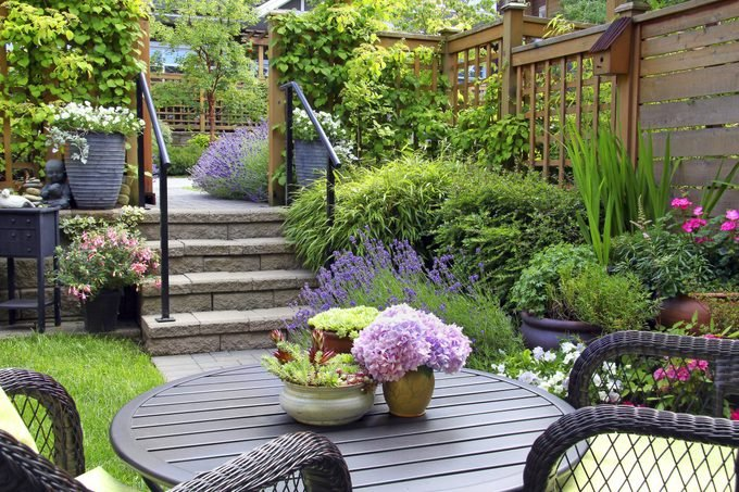 A lush patio garden with potted plants, trellises and perennials.
