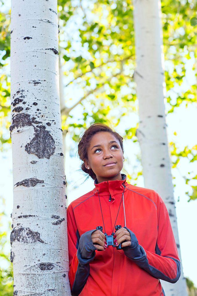 Mixed Race Girl Using Binoculars In Woods